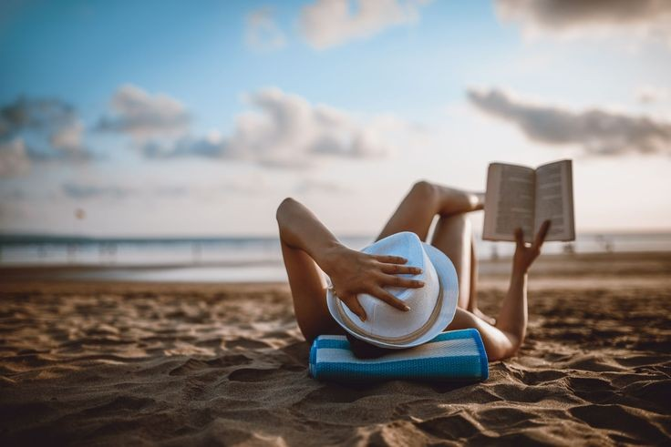 Relaxing at the beach while reading a book.